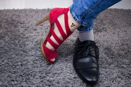 Personal has a lady`s boot on one foot, and on the other a male boot.The person has a third-gender tattoo.Man or woman? Person has woman´s red sandal and men´s black formal shoe.Gender conflict.