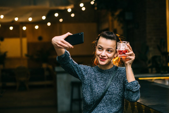Party, technology and holidays concept - happy smiling young pretty woman drinking scotch whiskey glass taking selfie at night club or pub