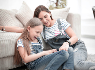 Mother with a little daughter using a smartphone sitting in the new living room
