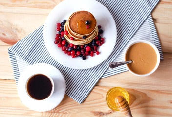 Flat  lay with pancakes, honey, peanut paste and coffee.