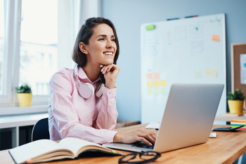 Young woman working in home office with laptop and smiling