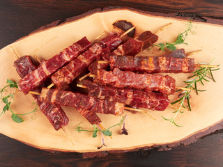 Raw fresh beef and lamb skewers, uncooked, on a wood board, garnished with fresh pea shoots and rosemary sprigs