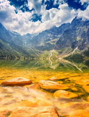Amazing nature, alpine lake in the mountains, scenic summer landscape with blue cloudy sky and reflection in the water, Morske Oko (Eye of the Sea), Tatra Mountains, Zakopane, Poland, vertical image