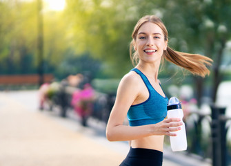 Happy woman with bottle of water, during morning jogging