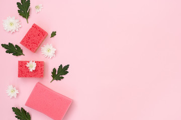 Pink cleaning sponges, white flowers and green leaves on pastel background Fototapete