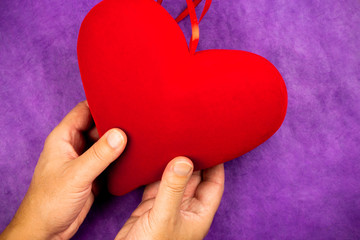 hand holding a big red heart on purple background
