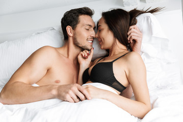 Young loving couple indoors in home in bed lies hugging and kissing.
