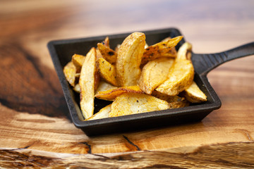 French fries in paper bag on wooden table close-up