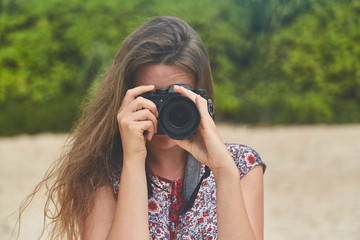 young girl taking pictures on camera in a summer on the beach