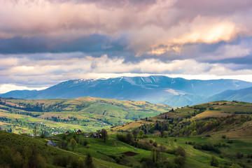 springtime countryside in mountain. grassy rural fields on hills. village in the valley. distant ridge with snowy tops. dramatic afternoon weather. cloudy sky