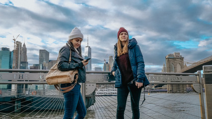 Two young women in New York walk along the typical skyline at Brooklyn Bridge