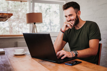 Young casual man working on a laptop