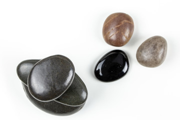 Black pebbles on white background with brown pebble.