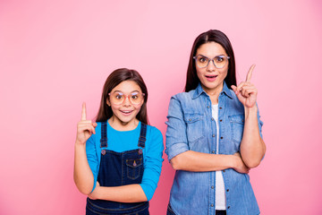 Portrait of two nice cute pretty lovely attractive charming funny brainy cheerful straight-haired girls pointing forefingers up good idea question answer decision isolated over pink pastel background