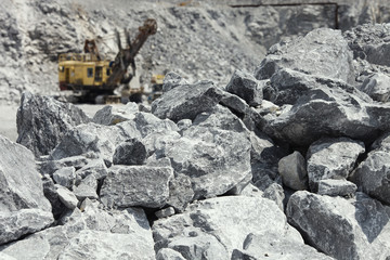 Large stones of rock ore with excavator in the background. Mining industry.