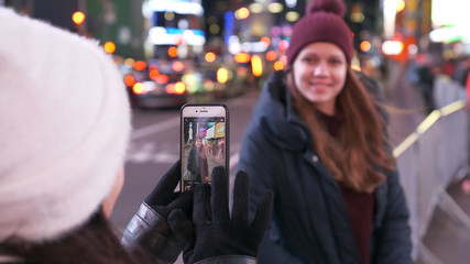 Two girls in New York take photos at Times Square