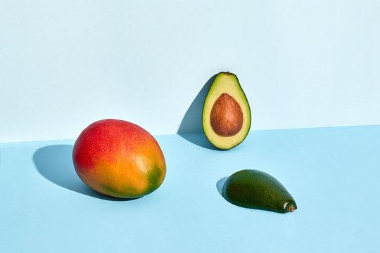 Avocado and mango fruits on blue background