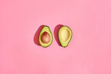 two half Avocado fruits on pink background