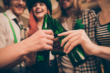 Cropped close up photo festive gathering company hands raise beer bottles toothy smiling laugh laughter bar pub celebrating funny funky carefree make take pictures every year tradition