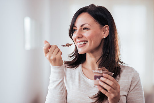Happy woman eating pudding.