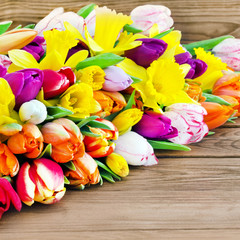 Tulips and daffodils against wooden background
