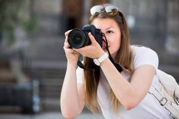 Cheerful girl is taking photos on her camera