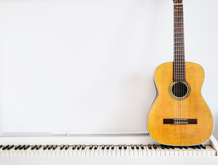 Acoustic guitar on piano keyboard in front of white wall.