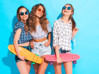 Three young stylish smiling beautiful girls with colorful penny skateboards. Woman in summer hipster checkered shirt clothes posing near blue wall in studio. Positive models having fun in sunglasses