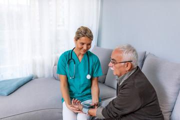 Happy senior man having his blood pressure measured in a nursing home by her caregiver. Happy nurse measuring blood pressure of a senior man in living room
