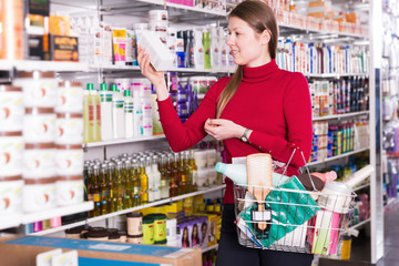 Young woman is looking hair care products, holding basket