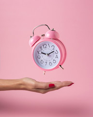 Alarm clock in a woman hand on a pink background. Minimal concept.