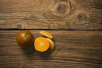 Wall Mural - Dark orange isolated on wooden background. Brown oranges.