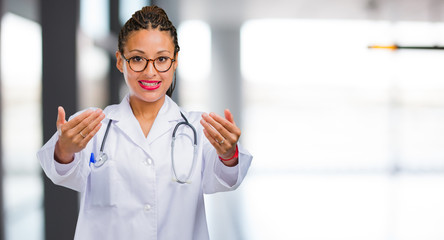 Portrait of a young black doctor woman inviting to come, confident and smiling making a gesture with hand, being positive and friendly