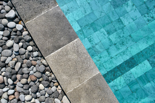 Closeup photo of pool edge which decorated with pebbles