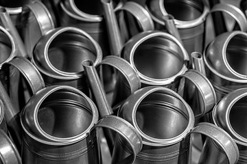 Rows of new metal garden watering can, soft focus, film grain - image