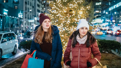 Two girls shop Christmas presents in New York