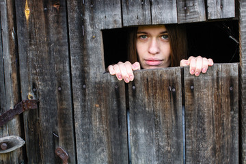 Woman locked in a wooden old barn, sad looks out the slit.