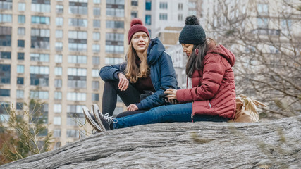 Two girls sit on a rock in Central Park New York