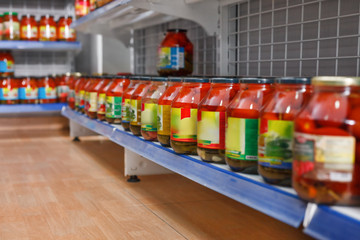 Different pickle goods at shelves in food store