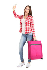 Young girl with suitcase making selfie on white background