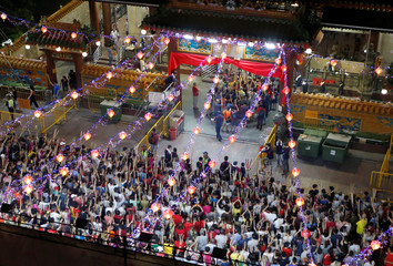 People wait to plant the first joss stick of the Lunar New Year of the Pig at the stroke of midnight at the Kwan Im Thong Hood Cho temple in Singapore