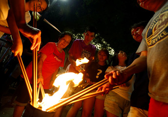 People burn joss sticks outside the Kwan Im Thong Hood Cho temple on the eve of the Lunar New Year of the Pig in Singapore