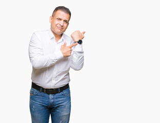 Middle age arab elegant man over isolated background In hurry pointing to watch time, impatience, upset and angry for deadline delay