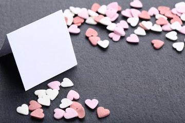 Heart shaped sprinkles with blank sheet of paper on black background