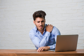 Young business man sitting and working on a laptop with back pain due to work stress, tired and astute Wall mural