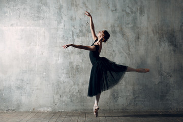 Ballerina female. Young beautiful woman ballet dancer, dressed in professional outfit, pointe shoes and black tutu.