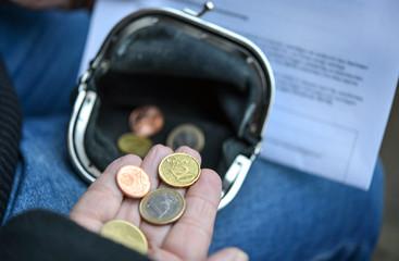 Ältere Frau zählt Kleingeld und hält Rentenbescheid in der Hand