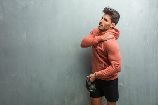 Young fitness man against a grunge wall with back pain due to work stress, tired and astute. Holding an iron dumbbell.