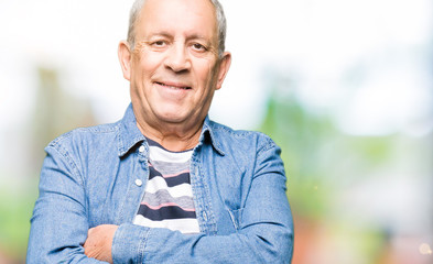 Handsome senior man wearing denim jacket happy face smiling with crossed arms looking at the camera. Positive person.