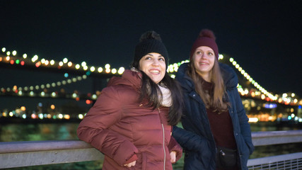 Two girls in New York enjoy the most beautiful place in the city at Brooklyn Bridge